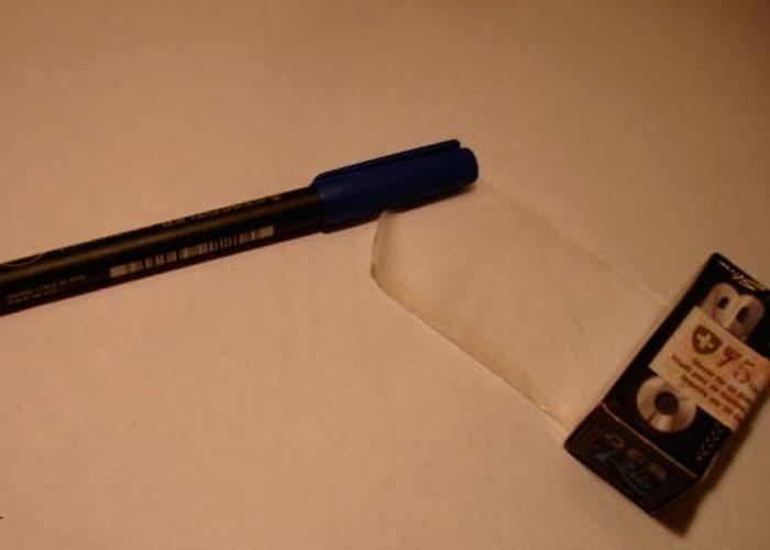 En la mesa ponemos el papel por la parte pegajosa hacia abajo, el bolígrafo de arriba